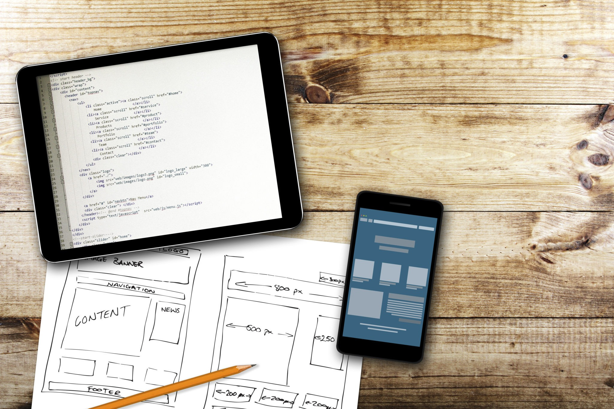 html coding on a tablet with website design sketches on paper