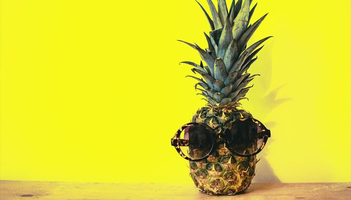 Pineapple with glasses in front of a bright yellow background.