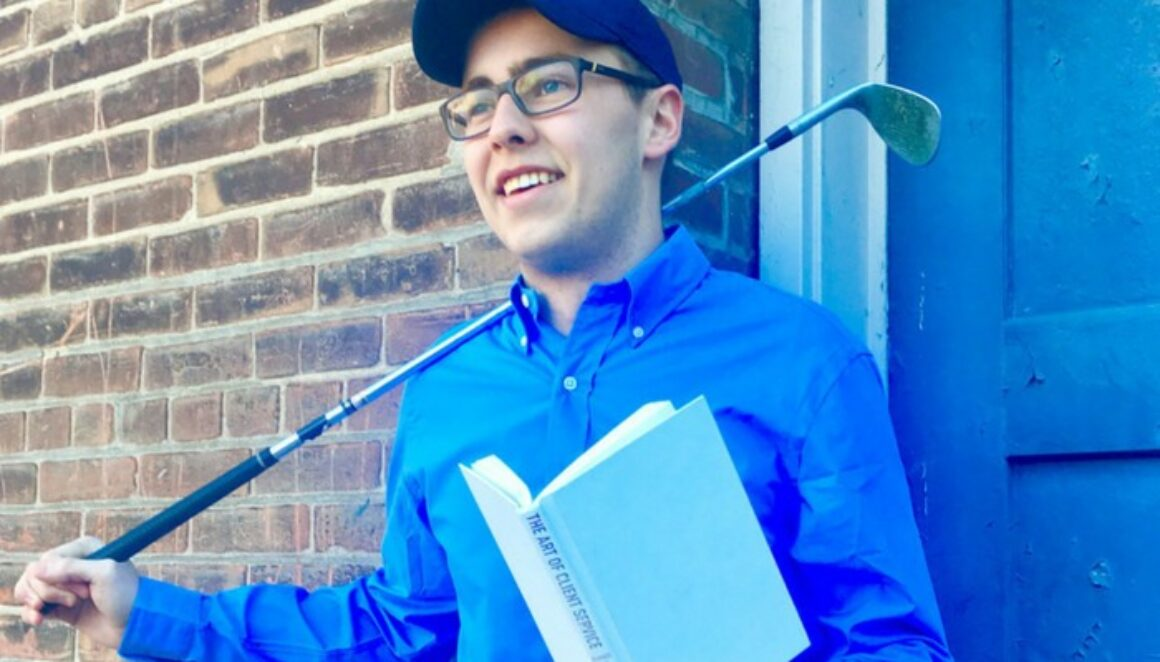 A photo of Bryce, an intern at The Blu Group, holding a book and golf club.