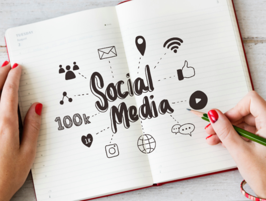 Person Looking at Notebook with Social Media Icons and Symbols