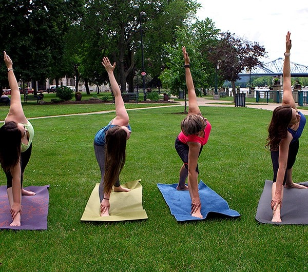 The BLÜ Group team de-stressing with team yoga in Riverside Park along the Mississippi River